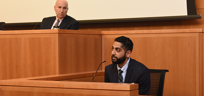 The mock trial's defendant, Dr. Rikin Shah, listens as Professor James Kainen, the trial's judge, looks on.