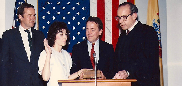 Amy Piro Chambers '74 being sworn in as judge, at the State House Annex in Trenton in 1986. From left, New Jersey Governor Thomas H. Kean, Chambers, her husband John W. Chambers, and New Jersey Supreme Court Justice Daniel J. O'Hern